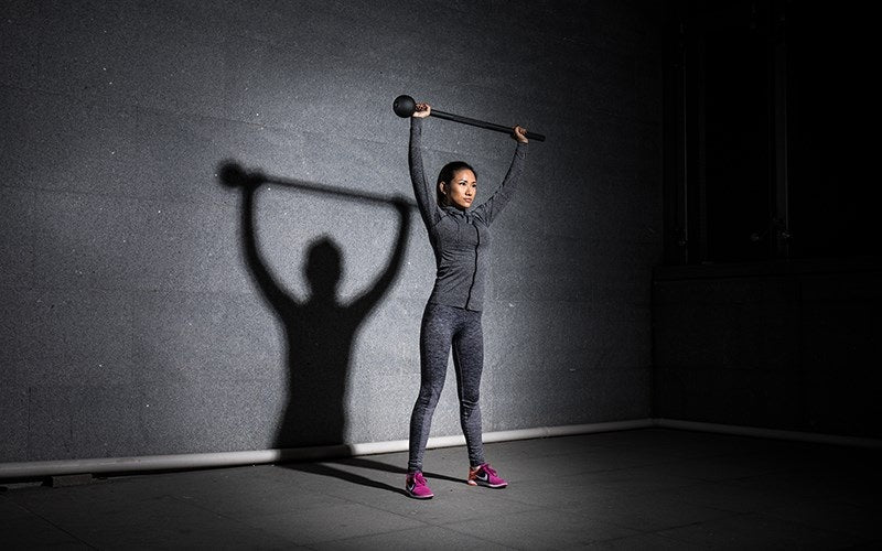 Woman holding a Steel Mace above her head in a overhead squat position