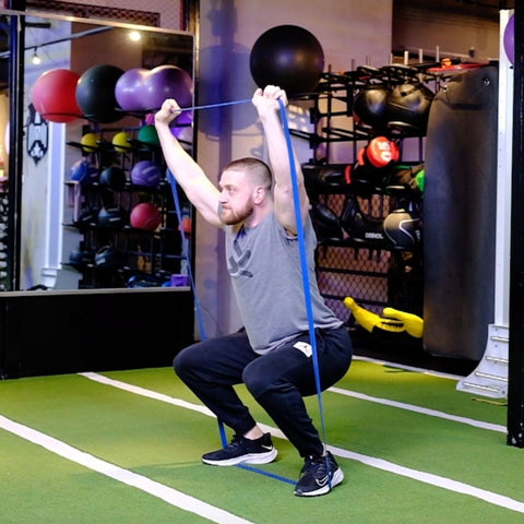 Where do you put resistance bands for squats