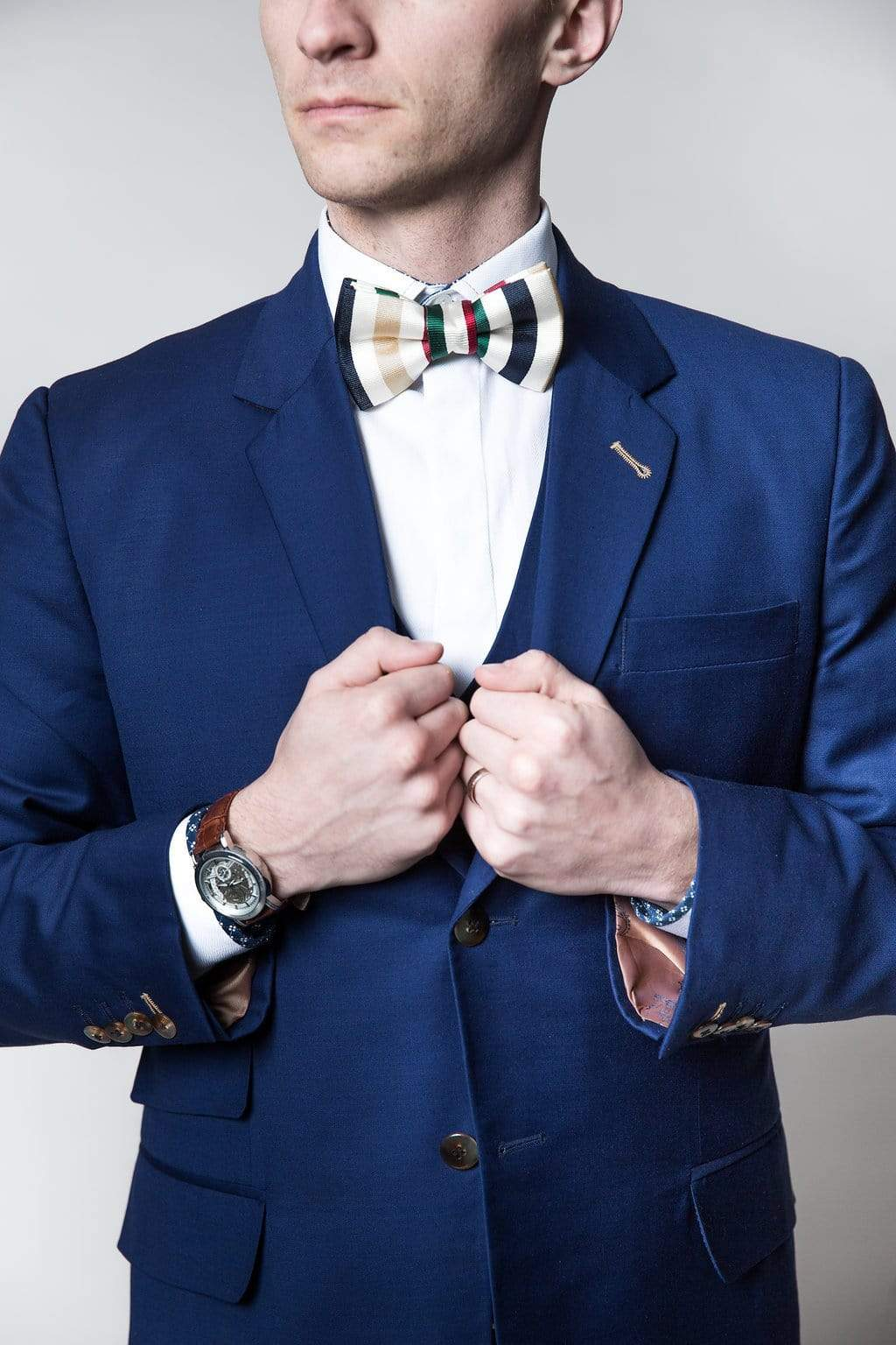 Man in a bespoke suit with a handmade bow tie grasping the lapels