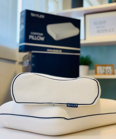 Skyler Pillows with packaging on bed