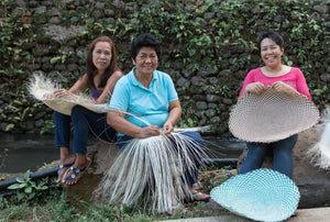 Smiling weavers weaving handbags made of natural plant fibers into eco-friendly artisanal handbags for fashion lifestyle women