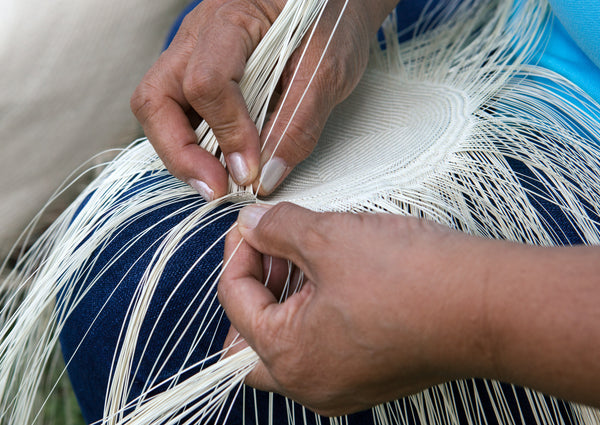 Hands weaving natural plant fiber into artisanal handmade handbags for fashion lifestyle women's purses and fashion accessories