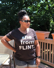 "lifestyle image of black woman standing with ""she from FLINT"" graphic t-shirt. Black shirt with white lettering."