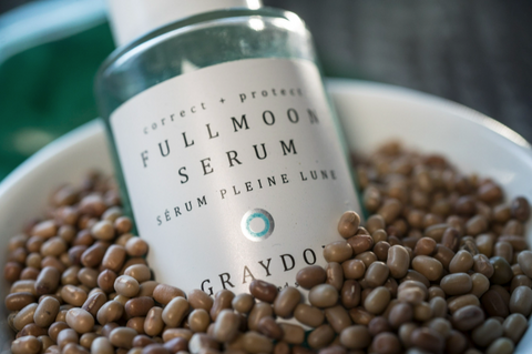 Bottle of Fullmoon Serum in a bowl of moth beans