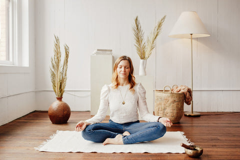 Melodie, founder of Elate Cosmetics, mediating on a white carpet next to a sound bowl