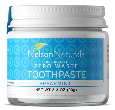 A zero-waste toothpaste in a glass container with a metal lid against a white background