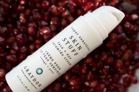 Bottle of Skin Stuff on a bed of pomegranate