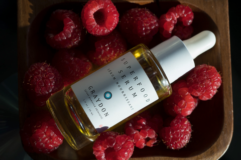 Bottle of Superfood Serum on a bed of raspberries