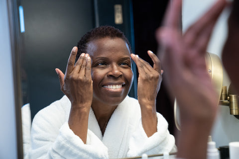 A dark-skinned woman in a white bathrobe cleansing her skin in front of a mirror