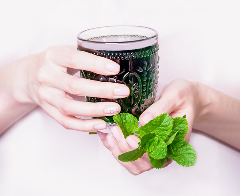 Woman's hands holding chlorophyll drink with mint leaves on white background