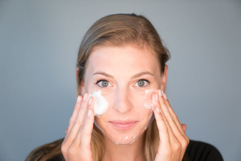 A woman cleansing her skin using a gently, fragrance-free foaming cleanser