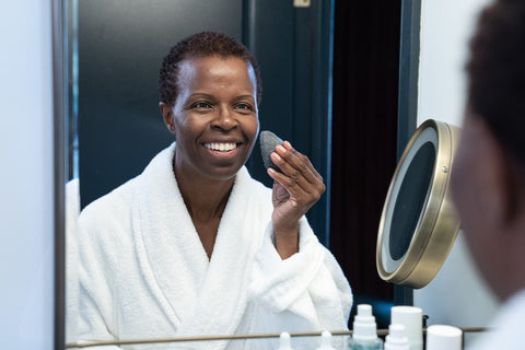 A dark-skinned woman in a comfortable white robe cleansing her skin in front of a mirror using a bamboo charcoal sponge
