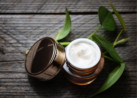 A chic jar of eye cream in glass packaging sitting on a wooden surface with greenery