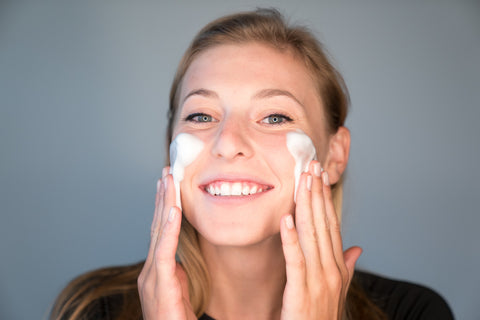 A smiling young woman applying Face Foam to her skin.