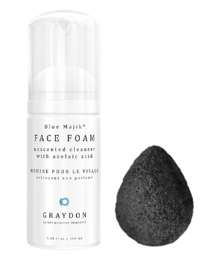 A bottle of foaming cleanser in a white bottle next to a black-coloured bamboo charcoal sponge against a white background