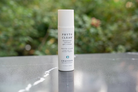 A natural face moisturizer containing squalane oil with greenery in the background