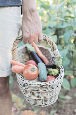 A young man with a basket full of vegetables