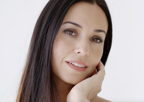 A headshot of a fair-skinned woman with dark hair and healthy-looking as she touches her left cheek with her left hand