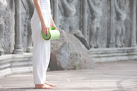 A young woman standing outside wearing white clothes and holding a green yoga mat