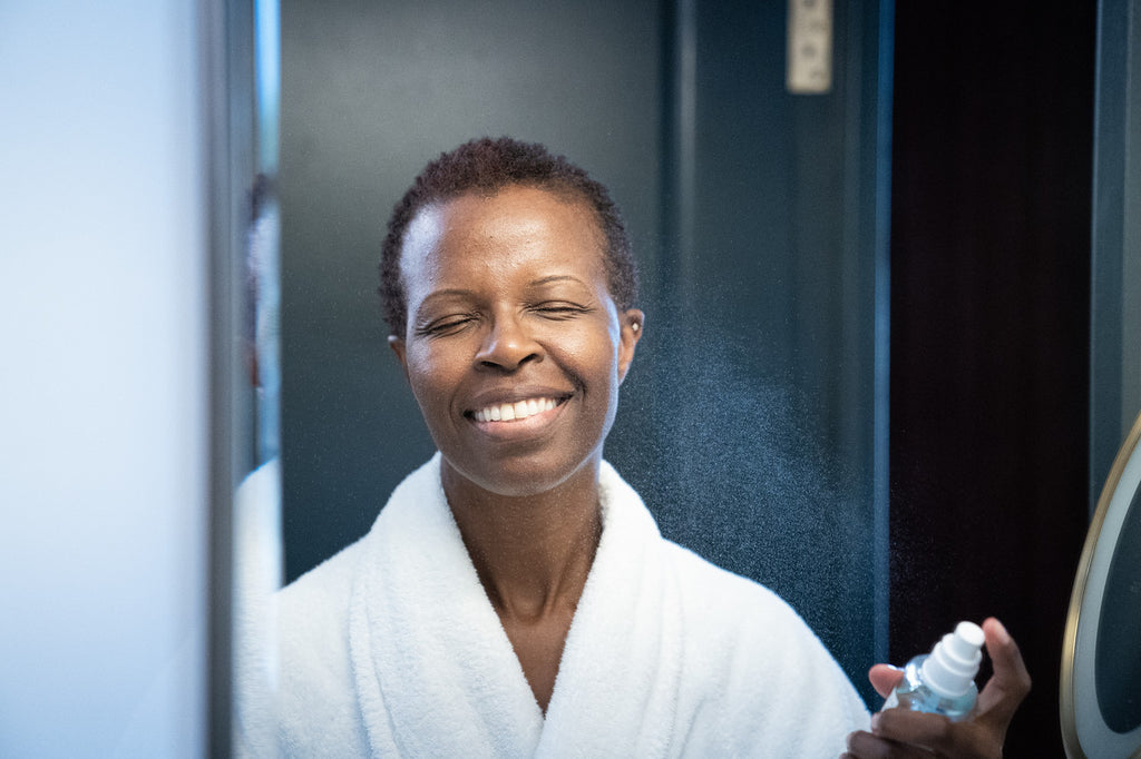 A smiling dark-skinned woman misting her face with an aquamarine-coloured vegan hydrating face mist in front of a mirror.