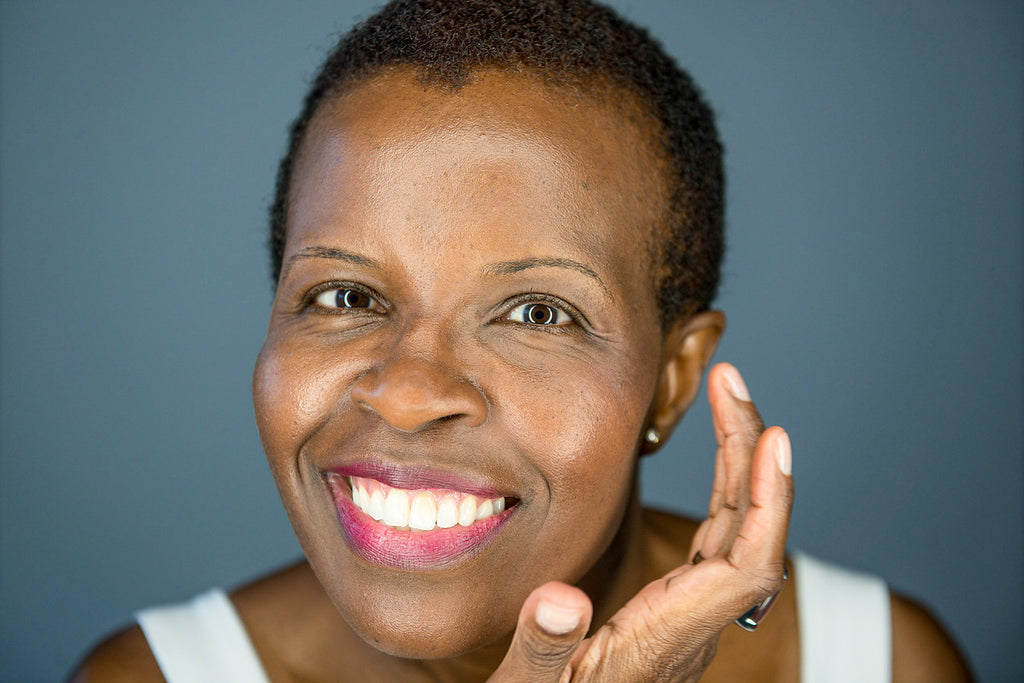 A smiling dark-skinned woman applying a tinted moisturizing skin primer with a blue-grey wall in the background.