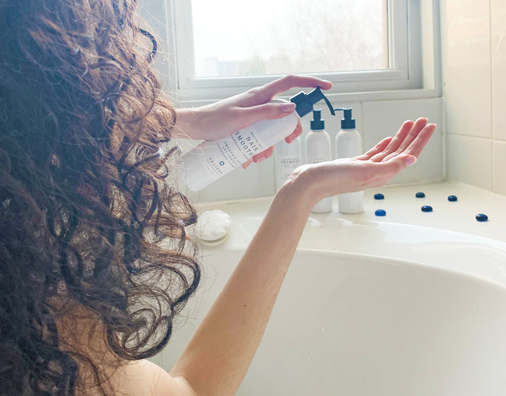 A woman with curly hair dispensing a detangling conditioner for sensitive scalp into her hand while sitting in a bathtub.