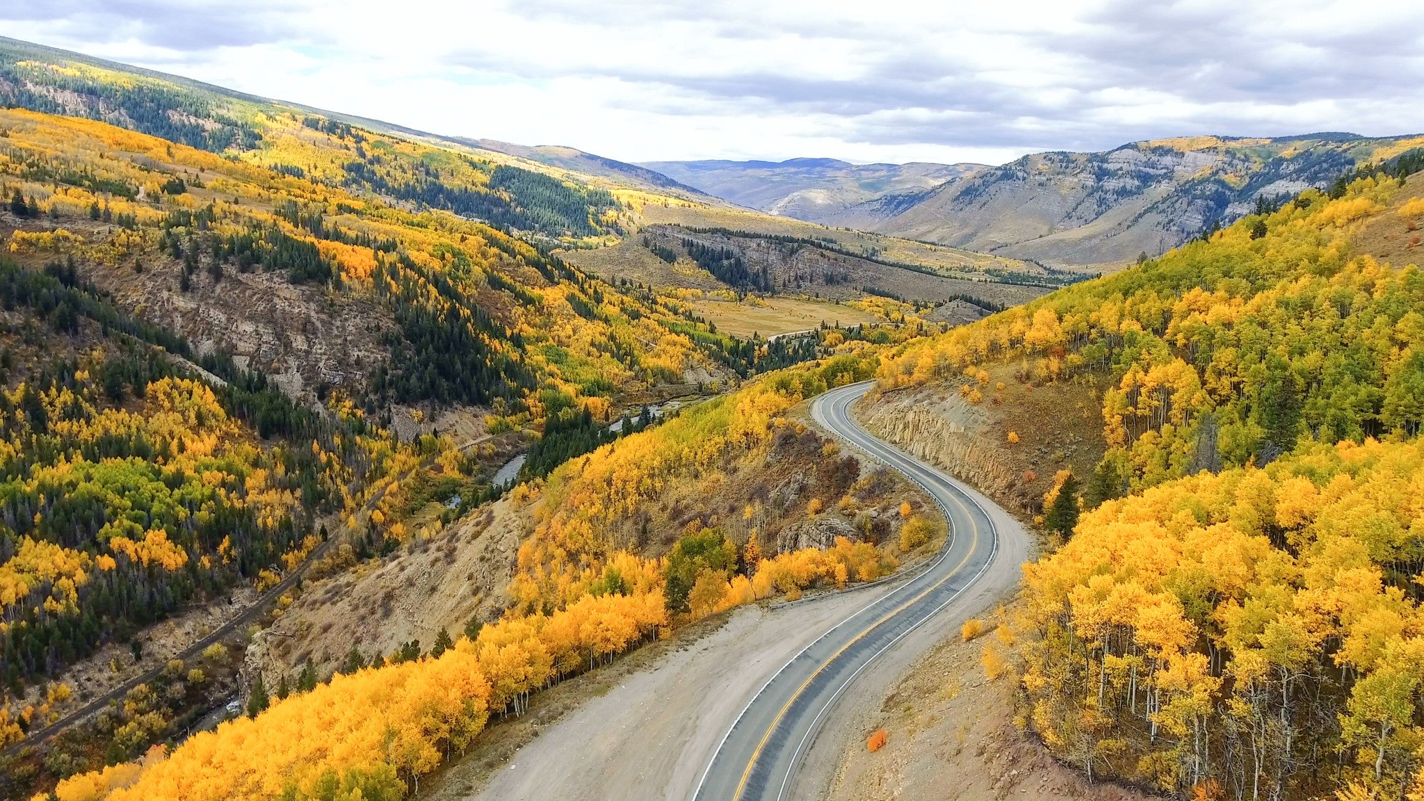 Winding road through Colorado Rocky Mountains and fall foliage