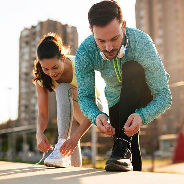 Couple in workout gear prepare for a run by securing their footwear