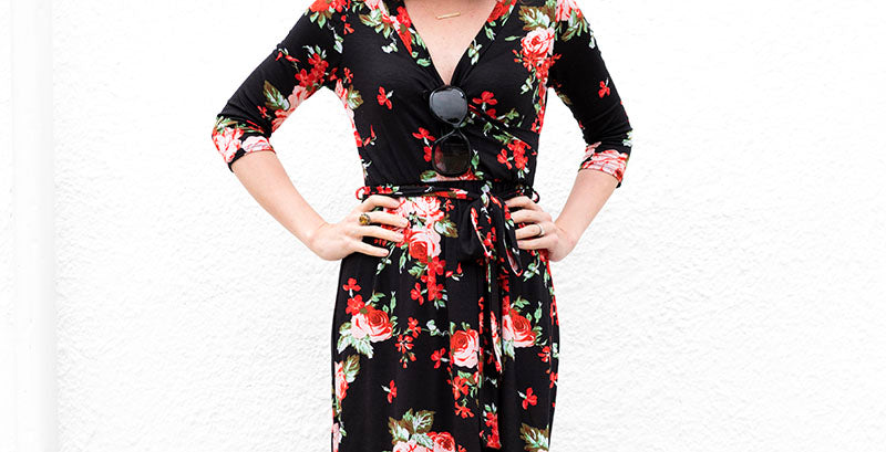 Woman in a black and red floral maxi dress with her hands on her hips.