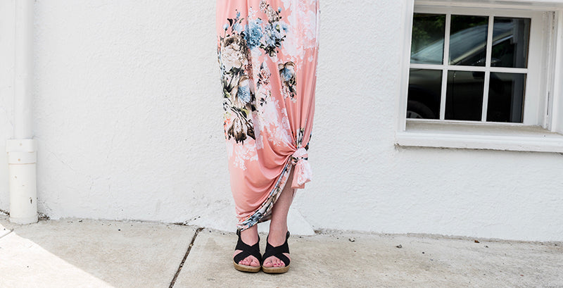 Woman's wearing a pink floral maxi dress with a knot tied to shorten the length, standing on the sidewalk in front of a white wall and window, with a purse and sunglasses on the sidewalk.