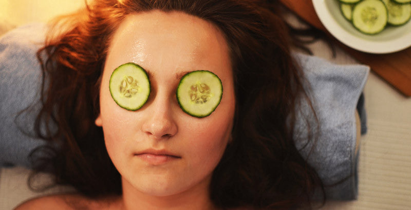 a lady that is getting a facial with cucumber slices on top of her eye while relaxing