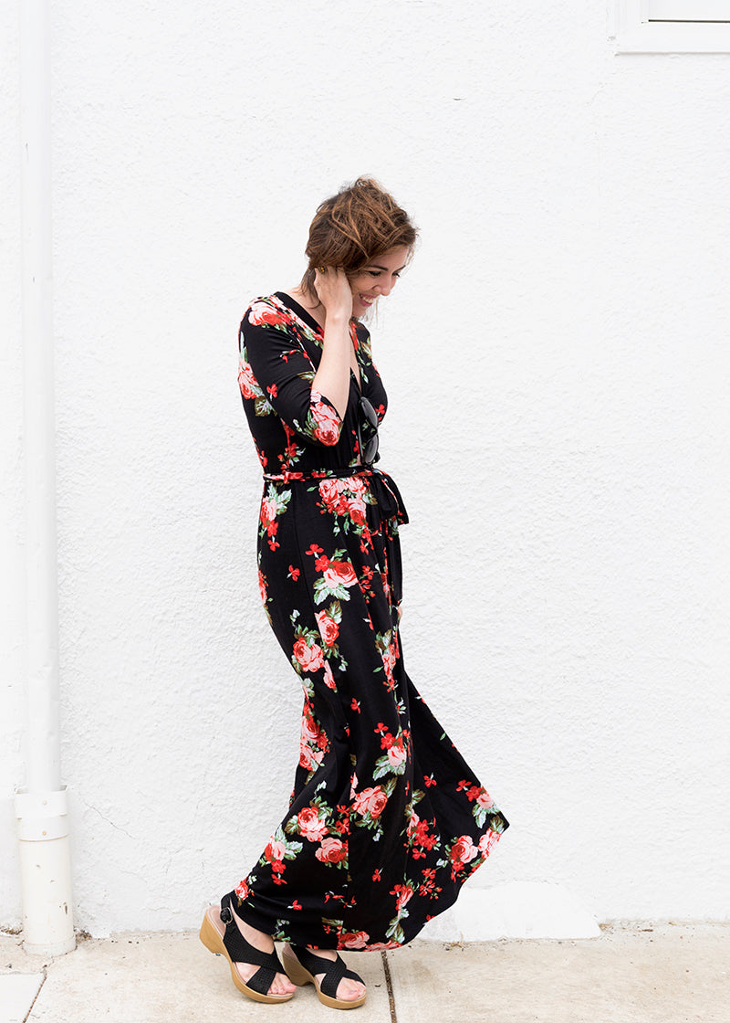 Brunette Woman in a black and red floral maxi dress standing in front of a white wall on the sidewalk, looking down while smiling, holding her hair to one side.
