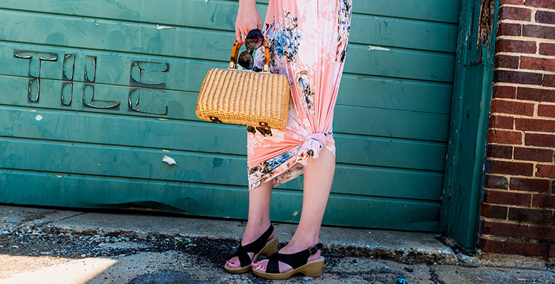 woman wearing a pink floral maxi dress tied in a knot at the knee, wearing slingback wedges holding a purse and sunglasses in one hand and her other hand on her hip, standing in front of a green weathered garage door with faded words on the street.