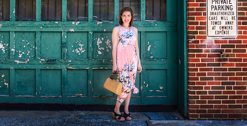 Woman smiling, wearing a pink floral maxi dress tied up at her knee to shorten the dress, wearing sling back wedges, posing in front of a green weathered down garage door and brick wall, holding a purse.