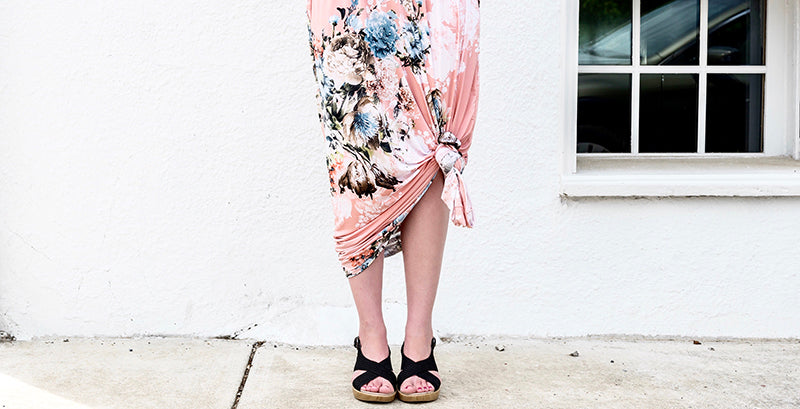 Woman wearing a pink floral maxi dress tied below the knee wearing sing back wedges with her hands on her hips standing on the sidewalk in front of a white wall and a window