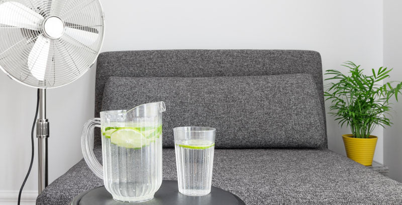 grey couch with table. on top of table ice cold water and pitcher in front of fan