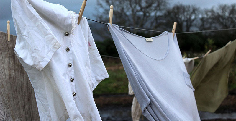 two stained white tops left out on the line to dry outdoors