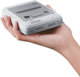 Hand holding SNES Classic Mini for size perspective