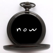 "Black compass with ""now"" written in white on the black face of the compass."