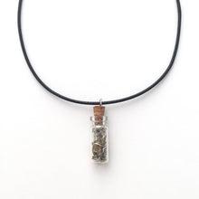Black artistic necklace with a charm that is a small bottle with broken clock pieces in it.