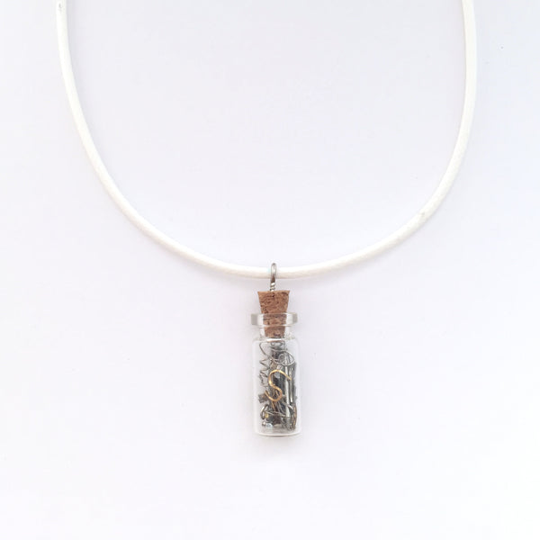 White artistic necklace with a charm that is a small bottle with broken clock pieces in it.