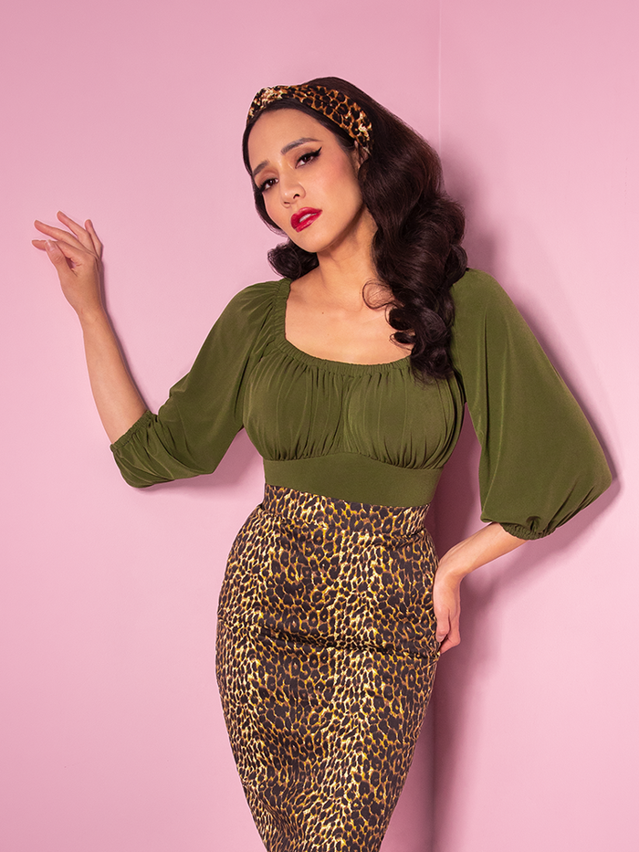 Milynn wearing a leopard print pencil skirt and the retro inspired Vacation Blouse in Olive Green from Vixen Clothing.