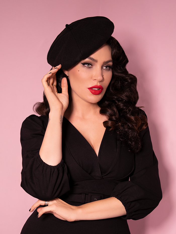 A closeup of Micheline Pitt modeling the Starlet beret in black paired with a matching black dress.
