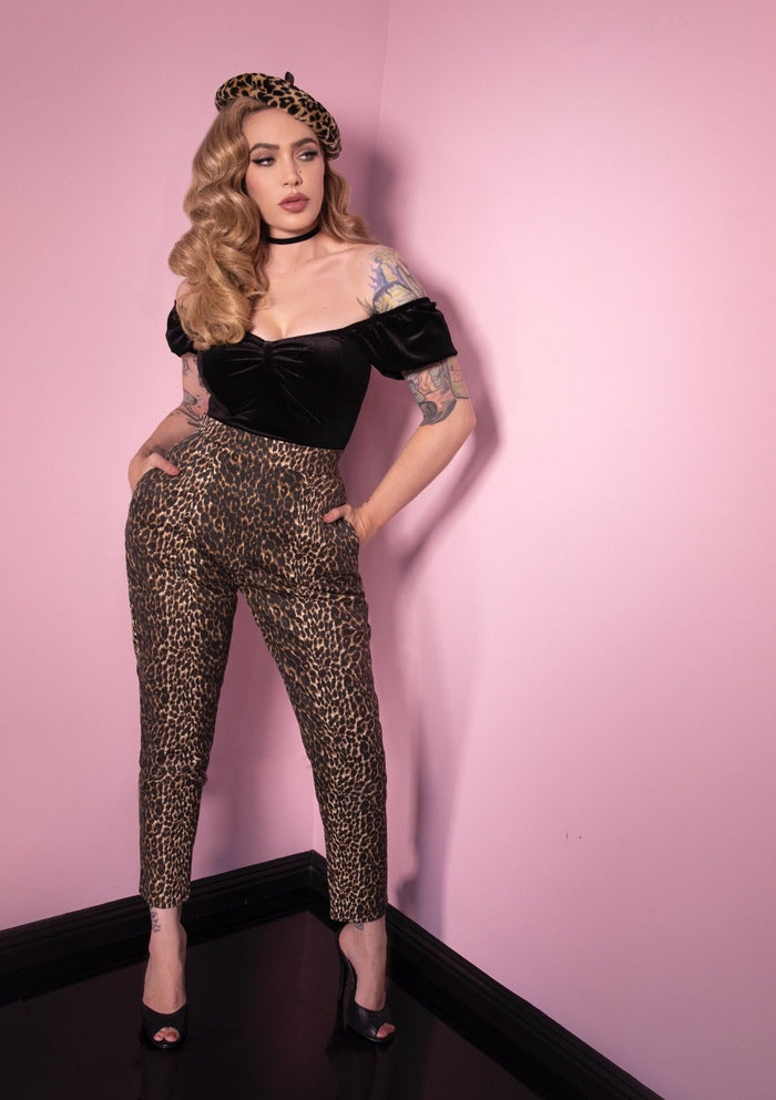 A full length shot of Micheline Pitt modeling the cigarette pants in leopard print by Vixen Clothing paired with a black top.