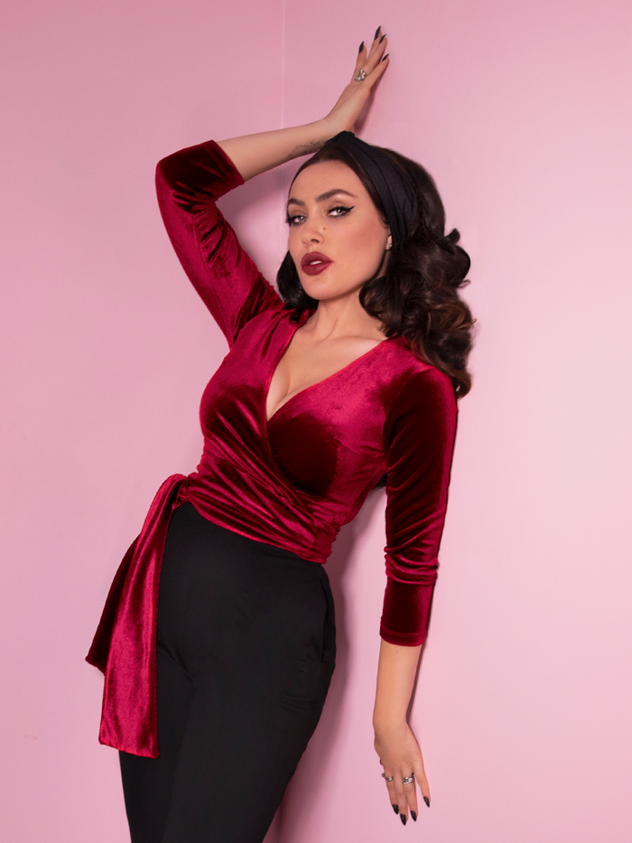 Micheline Pitt wearing the Wrap Top in Raspberry Red from Vixen Clothing.