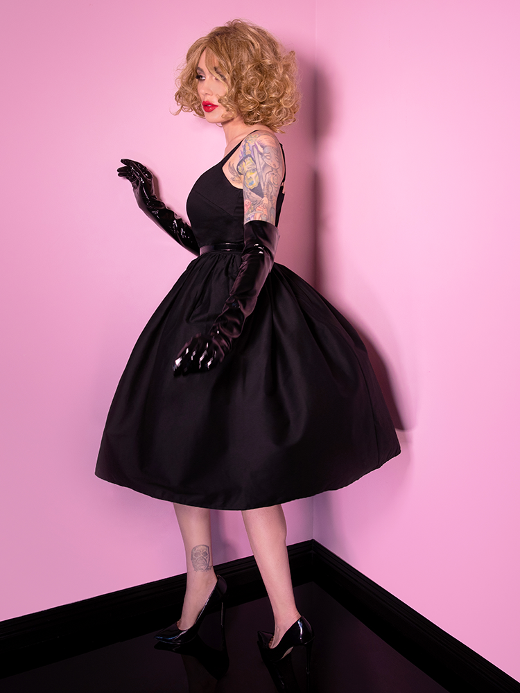 Profile shot of Micheline Pitt wearing the Miss Kitty 9 Lives Dress in Black.