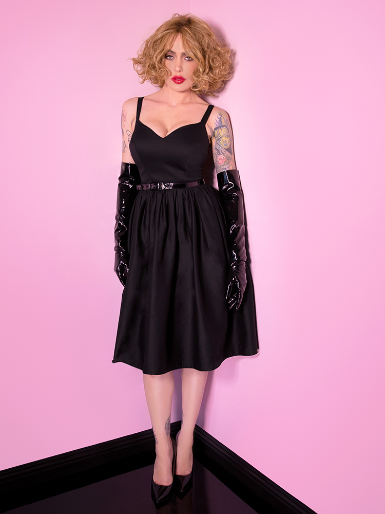 Micheline Pitt standing in the corner of her pink room wearing a vintage inspired dress with elbow length black vinyl gloves.