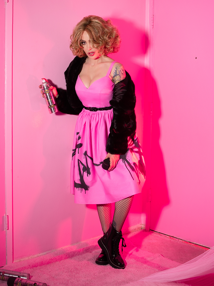 Holding a can of spray paint, Micheline Pitt looks ready to cause some mischief in her Miss Kitty 9 Lives Dress in Pink Spray Paint Print dress, fishnet stockings and black vinyl ankle boots.