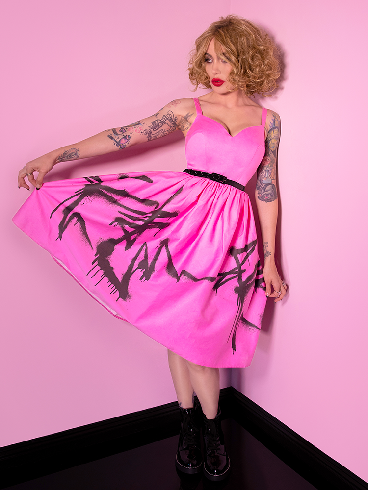 Micheline Pitt stretching out the skirt section of her Miss Kitty 9 Lives Dress in Pink Spray Paint Print to show off the color and design.