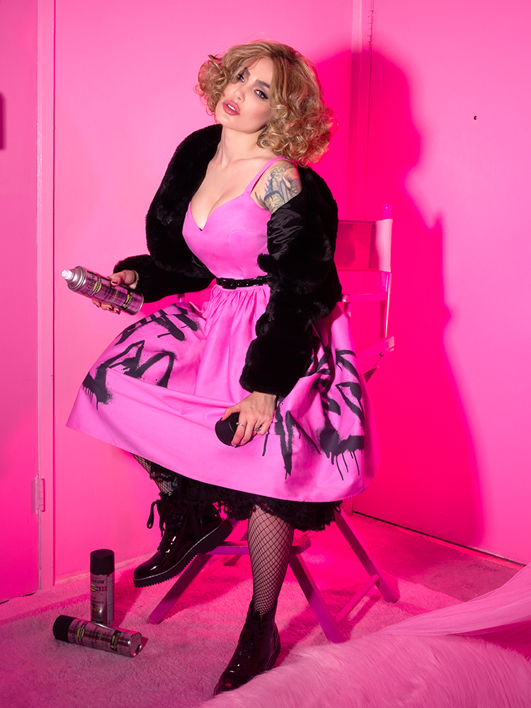 Sitting on a step stool and holding a can of spray paint, Micheline Pitt shows off the latest vintage inspired dress from Vixen clothing.